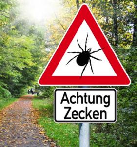 Ein Schild im Wald warnt vor Zecken